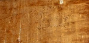 Names and dates carved into the wood